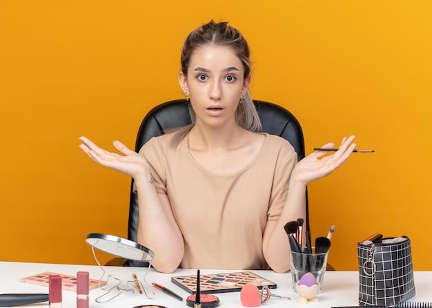 Verrast jong mooi meisje zit aan tafel met make-uptools met make-upborstel die handen verspreidt die op een oranje achtergrond zijn geïsoleerd