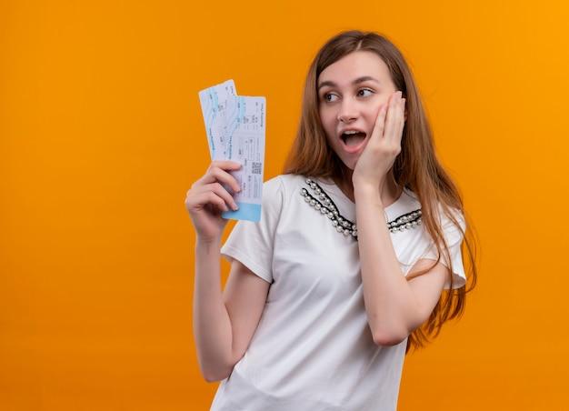 Verrast jong reizigersmeisje die vliegtuigtickets houden die hand op wang op geïsoleerde oranje muur met exemplaarruimte zetten