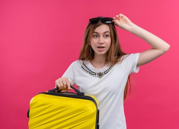 Verrast jong reizigersmeisje die zonnebril op hoofd dragen die koffer houden en de hand op zonnebril zetten op geïsoleerde roze muur