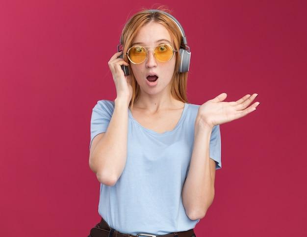 Verrast jong roodharige gembermeisje met sproeten in zonnebril en op koptelefoon met hand open geïsoleerd op roze muur met kopieerruimte