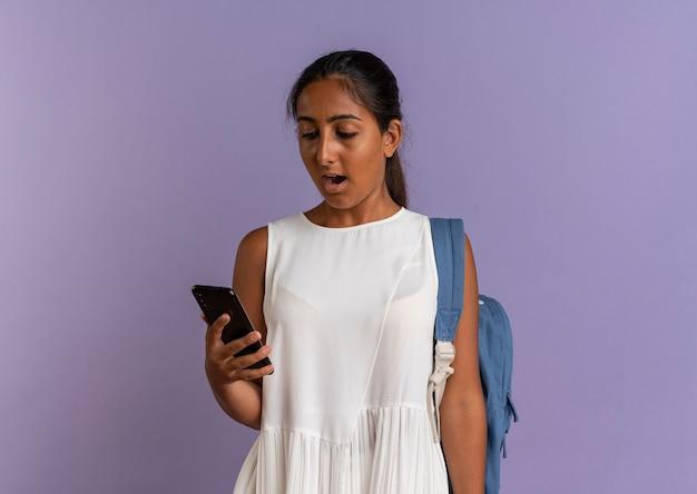 Verrast jong schoolmeisje die rugtas draagt en telefoon op paars bekijkt