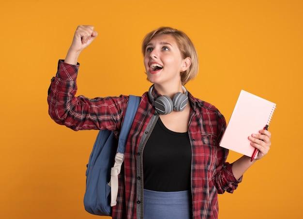 Verrast jong slavisch studentenmeisje met koptelefoon met rugzakstandaards met opgeheven vuist houdt notitieboekje en pen vast die naar de zijkant kijken