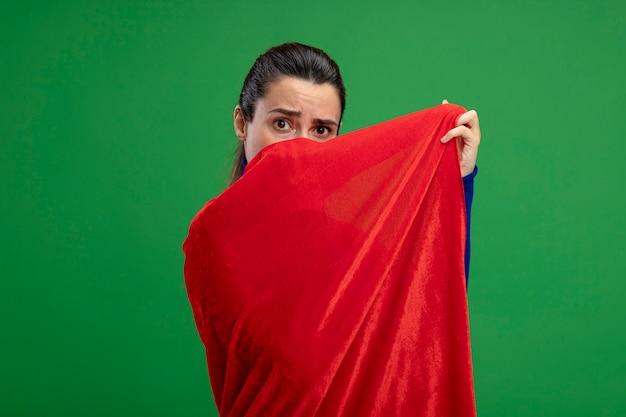 Verrast jong superheld meisje bedekt gezicht met mantel geïsoleerd op groen