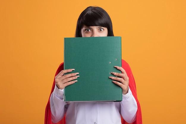 Verrast jong superheld meisje draagt een stethoscoop met medische mantel en mantel bedekt gezicht met map