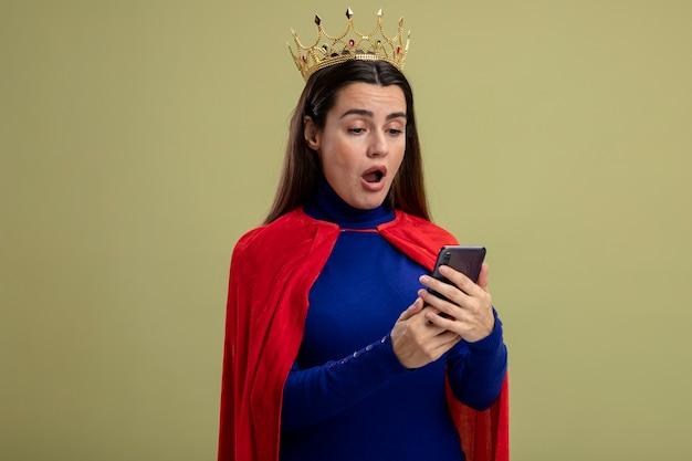 Verrast jong superheld meisje dragen kroon houden en kijken naar telefoon geïsoleerd op olijfgroen
