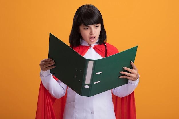 Verrast jong superheld meisje dragen stethoscoop met medische mantel en mantel houden en kijken naar map
