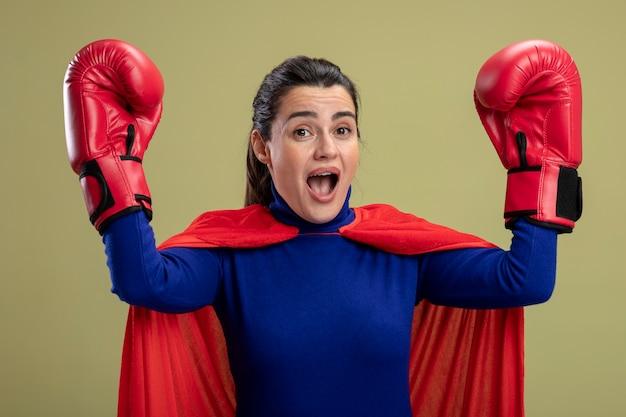 Verrast jong superheromeisje die bokshandschoenen dragen die handen opheffen die op olijfgroen worden geïsoleerd