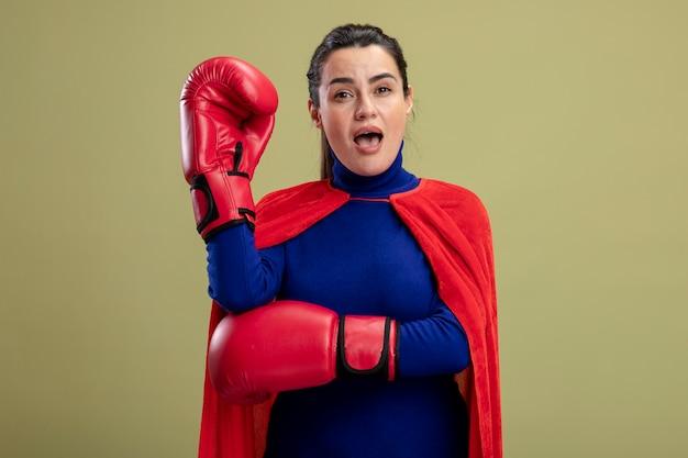 Verrast jong superheromeisje die bokshandschoenen dragen die vuist opheffen die op olijfgroene achtergrond wordt geïsoleerd