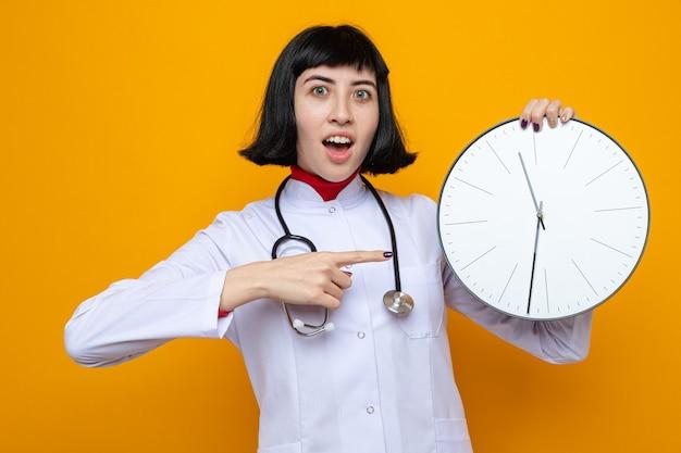 Verrast jong, vrij blank meisje in doktersuniform met een stethoscoop die vasthoudt en naar de klok wijst