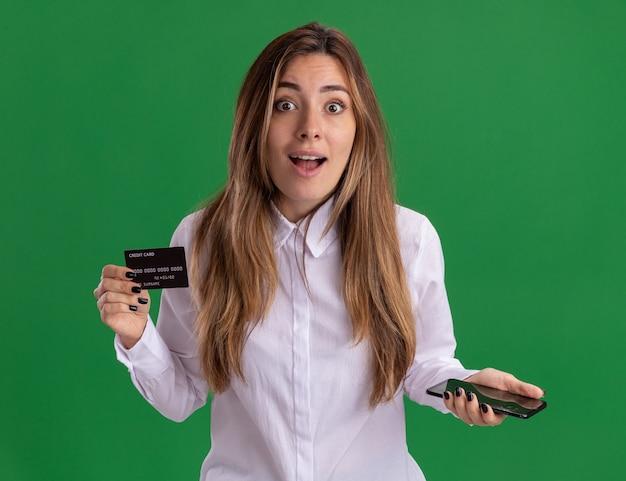 Verrast jong, vrij kaukasisch meisje houdt creditcard en telefoon geïsoleerd op een groene muur met kopieerruimte