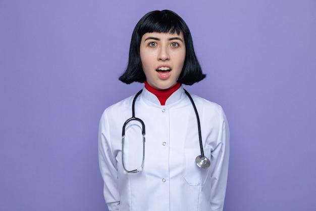Verrast jong, vrij kaukasisch meisje in doktersuniform met een stethoscoop die staat en
