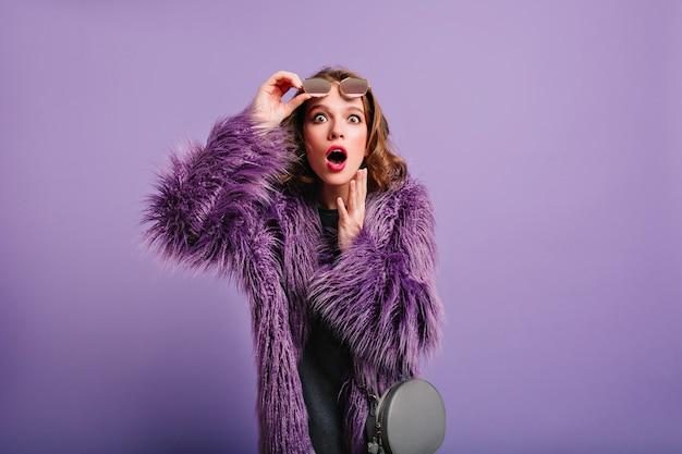 Verrast jong vrouwelijk model met elegante grijze tas poseren in paarse studio