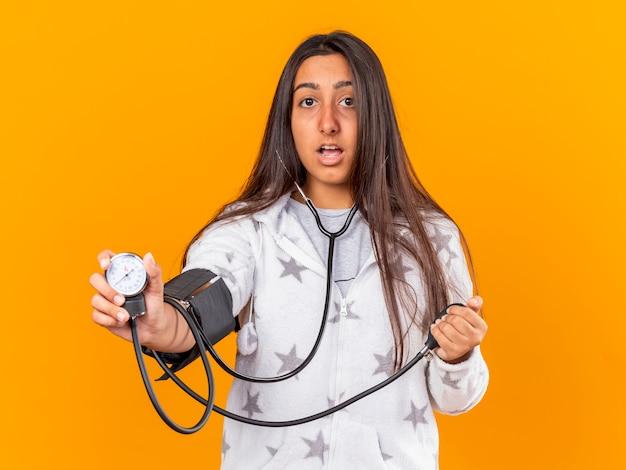 Verrast jong ziek meisje haar eigen druk meten met bloeddrukmeter geïsoleerd op gele achtergrond