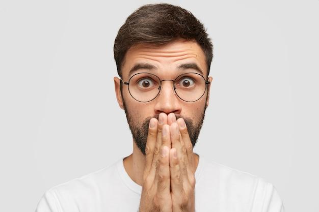 Verrast jonge aantrekkelijke man bedekt mond en kijkt met een ongelooflijke uitdrukking