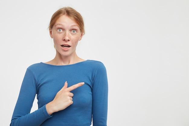 Verrast jonge aantrekkelijke roodharige dame die haar groene ogen rondt terwijl ze verbaasd naar de camera kijkt, opzij toont met wijsvinger terwijl ze op een witte achtergrond staat