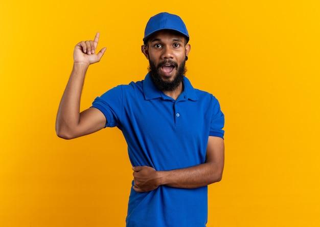 Verrast jonge afro-amerikaanse bezorger die omhoog wijst geïsoleerd op een oranje achtergrond met kopieerruimte