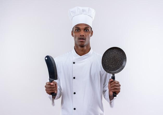 Verrast jonge afro-amerikaanse kok in uniform chef houdt mes en koekenpan op geïsoleerde witte achtergrond met kopie ruimte
