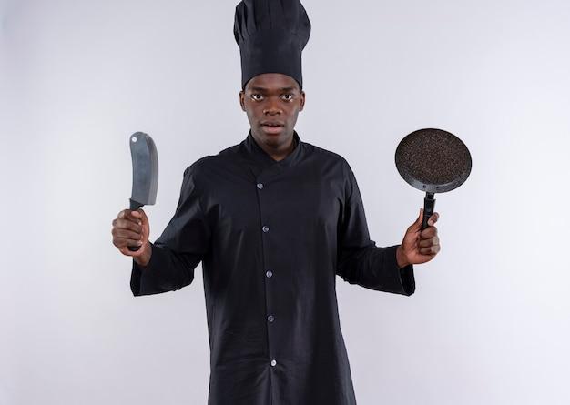 Verrast jonge afro-amerikaanse kok in uniform chef houdt mes en koekenpan op wit met kopie ruimte