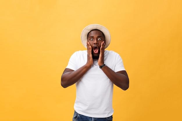 Verrast jonge afro-amerikaanse man met een casual grijs t-shirt camera staren met een geschokte blik, verbazing en shock uiten.