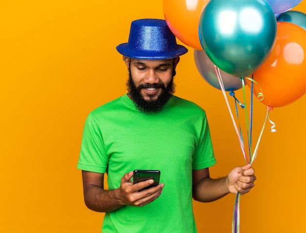 Verrast jonge afro-amerikaanse man met een feesthoed die vasthoudt en naar een telefoon kijkt die op een oranje muur is geïsoleerd
