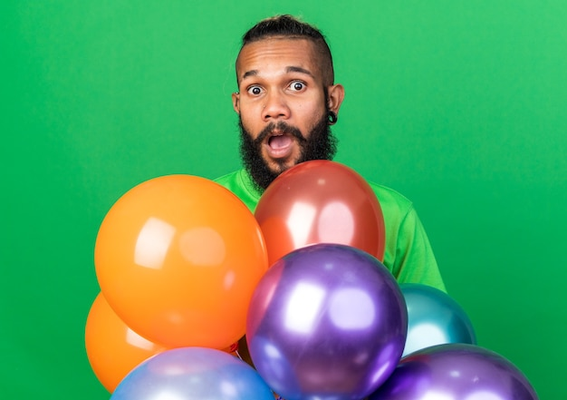 Verrast jonge afro-amerikaanse man met een groen t-shirt achter ballonnen geïsoleerd op een groene muur