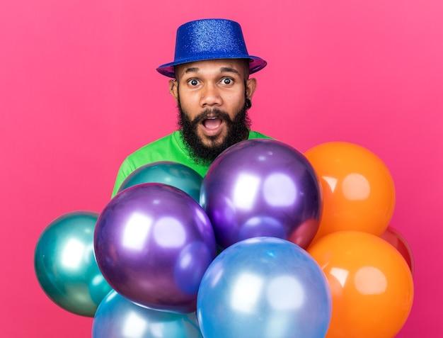 Verrast jonge afro-amerikaanse man met feestmuts achter ballonnen geïsoleerd op roze muur