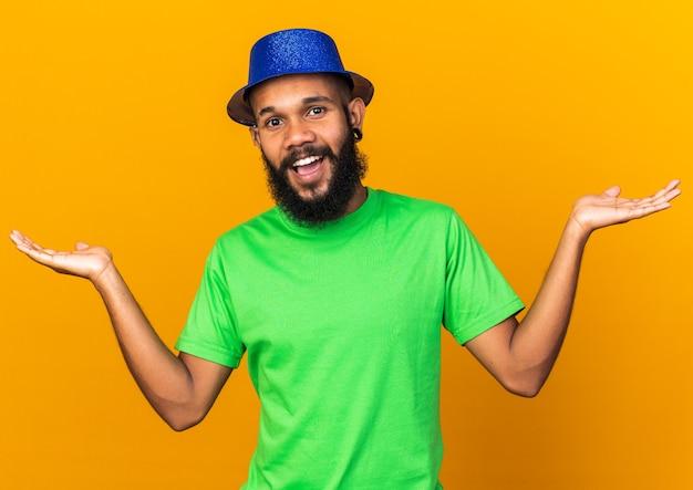 Verrast jonge afro-amerikaanse man met feestmuts die handen uitspreidt
