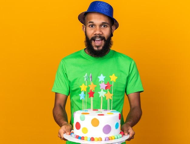 Verrast jonge afro-amerikaanse man met feestmuts die taart op camera steekt