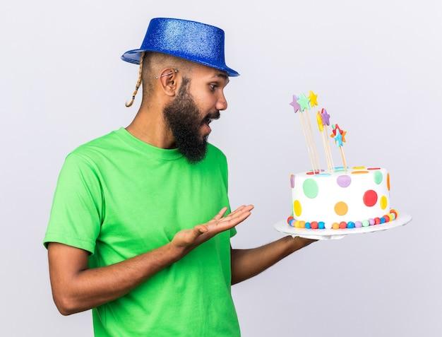 Verrast jonge afro-amerikaanse man met feestmuts en wijst naar cake