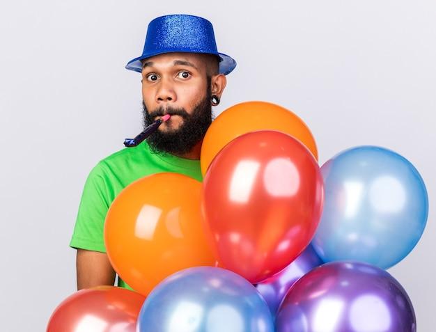 Verrast jonge afro-amerikaanse man met feestmuts met ballonnen die feestfluitje blazen