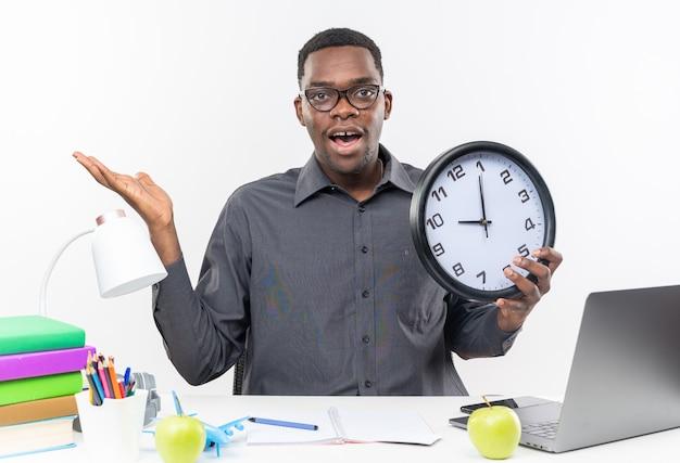 Verrast jonge afro-amerikaanse student in optische bril zittend aan een bureau met school tools houden klok en houden hand open geïsoleerd op witte muur