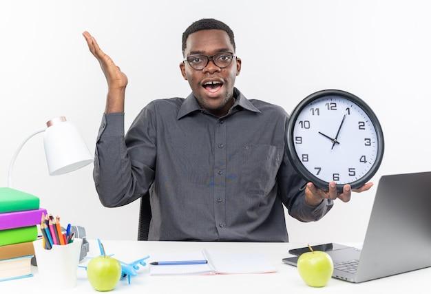 Verrast jonge afro-amerikaanse student in optische bril zittend aan een bureau met schoolhulpmiddelen die de hand opsteken en de klok vasthouden