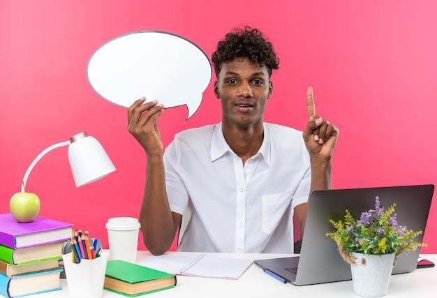 Verrast jonge afro-amerikaanse student zit aan een bureau met schoolhulpmiddelen die een tekstballon vasthouden en naar boven wijzen