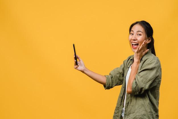 Verrast jonge aziatische dame met behulp van mobiele telefoon met positieve uitdrukking, glimlacht breed, gekleed in casual kleding en staat geïsoleerd op gele muur. gelukkige schattige blije vrouw verheugt zich over succes.