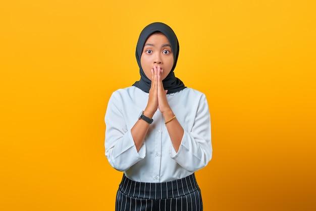 Verrast jonge aziatische vrouw die mond bedekt met handen geïsoleerd over gele achtergrond