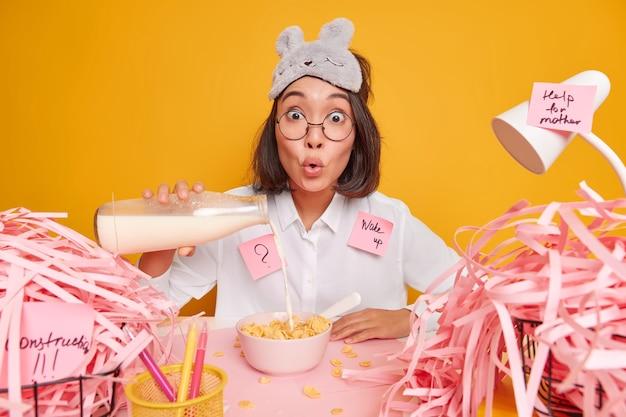 Verrast jonge aziatische vrouw giet melk in cornflakes bereidt ontbijt maakt memo stickers heeft rotzooi op desktop geïsoleerd over gele muur heeft een druk schema
