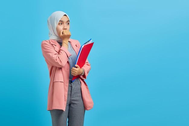 Verrast jonge aziatische vrouw met map en kijken naar lege ruimte over blauwe achtergrond