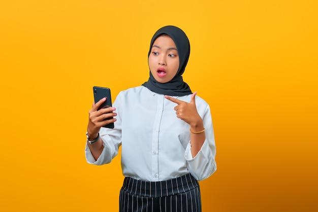Verrast jonge aziatische vrouw wijzend op mobiele telefoon geïsoleerd op gele achtergrond