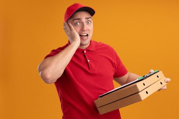 Verrast jonge bezorger die uniform met pet draagt die pizzadozen met klembord houdt die hand op wang zetten die op oranje muur wordt geïsoleerd