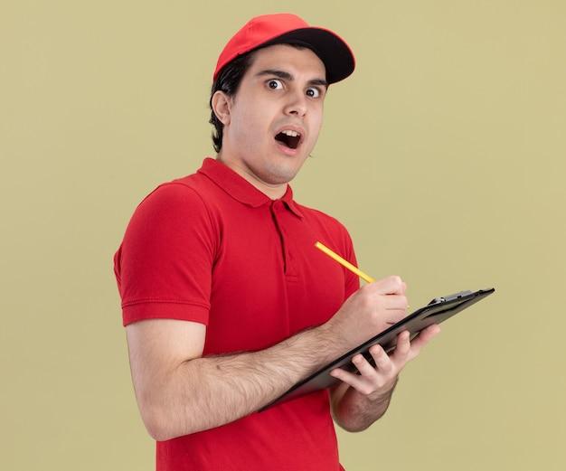 Verrast jonge bezorger in rood uniform en pet met potlood en klembord kijkend naar voorkant geïsoleerd op olijfgroene muur