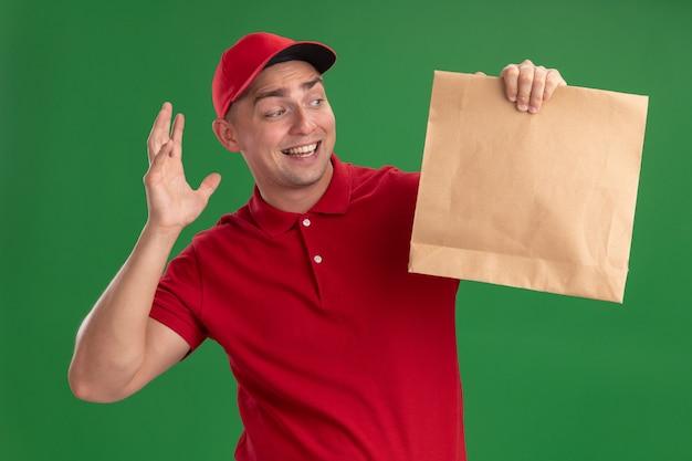 Verrast jonge bezorger met uniform en pet houden en kijken naar papier voedselpakket geïsoleerd op groene muur