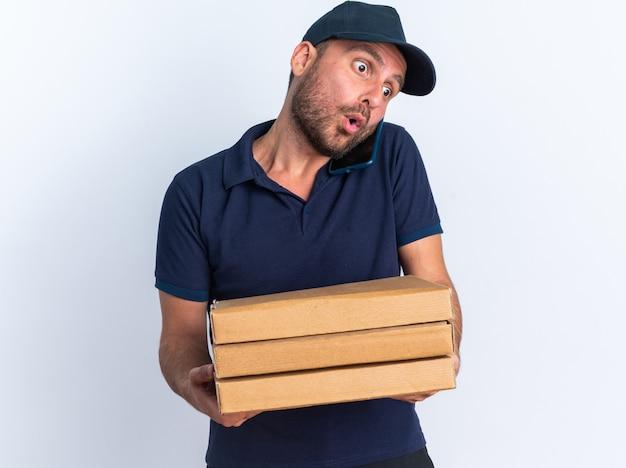 Verrast jonge blanke bezorger in blauw uniform en pet met pizzapakketten pratend aan de telefoon en neerkijkend op een witte muur