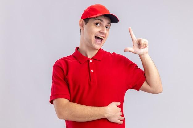 Verrast jonge blanke bezorger in rood shirt die omhoog wijst