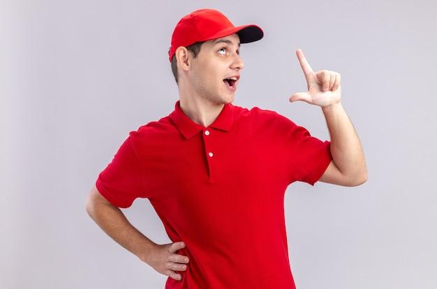 Verrast jonge blanke bezorger in rood shirt kijken en omhoog wijzend geïsoleerd op een witte muur met kopieerruimte