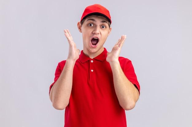 Verrast jonge blanke bezorger in rood shirt staande met opgeheven handen