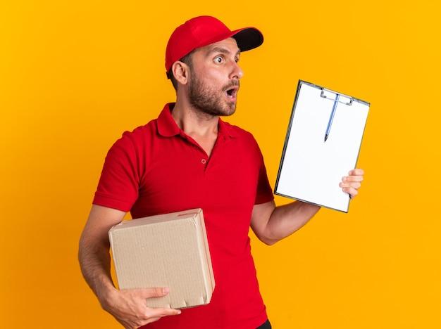 Verrast jonge blanke bezorger in rood uniform en pet met kartonnen doos en klembord kijkend naar de zijkant
