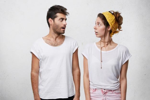 Verrast jonge blanke man en vrouw kijken elkaar vol ongeloof aan, met verbaasde blikken. positieve menselijke gezichtsuitdrukkingen, emoties, gevoelens, houding en reactie