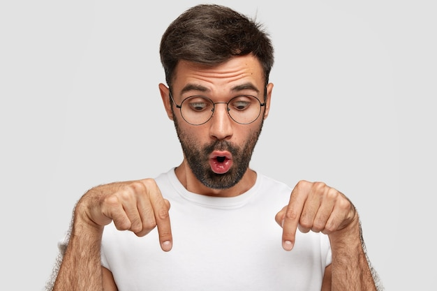 Verrast jonge blanke man met afgeluisterde ogen en geopende mond, wijst met beide wijsvingers naar beneden, merkt iets ongelooflijks op, draagt een ronde bril, geïsoleerd over een witte muur.