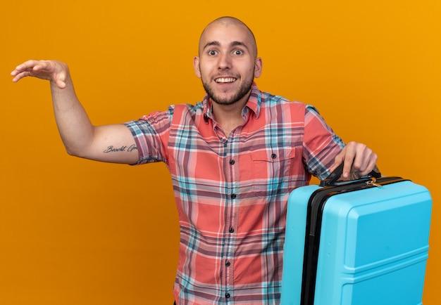 Verrast jonge blanke reiziger die koffer vasthoudt en hand open houdt geïsoleerd op oranje muur met kopieerruimte wall