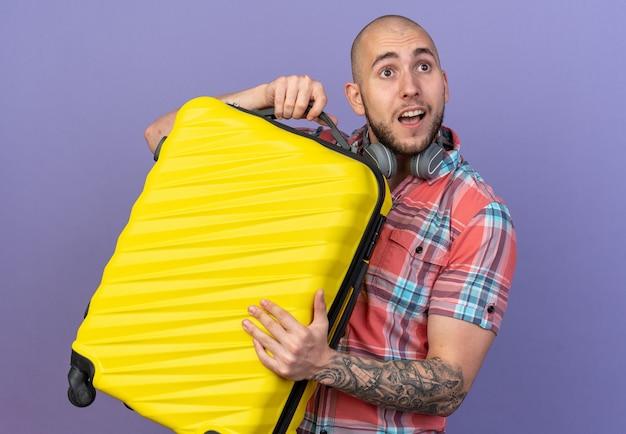 Verrast jonge blanke reiziger man met koptelefoon om zijn nek met koffer kijkend naar kant geïsoleerd op paarse muur met kopieerruimte